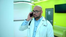 Доктор человека говоря на телефоне Доктор говоря на телефоне Мужской доктор говоря на конце телефона вверх Портрет  акции видеоматериалы