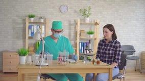 Доктор человека принимает анализ слюны от рта молодой женщины с пробиркой хлопка сток-видео
