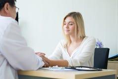 Доктор человека рук успокаивая к счастливому женскому пациенту и давая консультацию и поощрение на больнице стоковые изображения