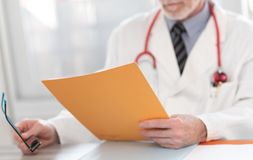 Доктор читая медицинское заключение стоковые изображения