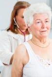 Доктор auscultating старший пациент на практике Стоковые Изображения