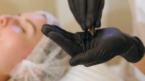Доктор Beautician в черных стерильных перчатках раскрывает ампулу с hyaluronic кислотой акции видеоматериалы