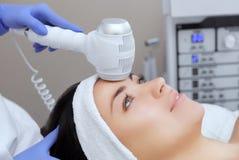 Доктор-cosmetologist делает процедуру по Cryotherapy лицевой кожи красивого, молодой женщины в салоне красоты стоковое изображение