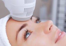 Доктор-cosmetologist делает процедуру Cryotherapy лицевой кожи красивого, молодой женщины в салоне красоты стоковые изображения rf