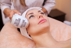Доктор-cosmetologist делает процедуру Cryotherapy лицевой кожи красивого, молодой женщины в салоне красоты стоковое изображение rf