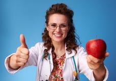 Доктор Paediatrician давая яблоко и показывая большие пальцы руки вверх Стоковое фото RF