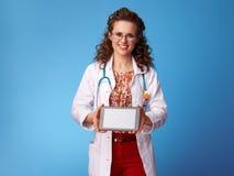 Доктор Paediatrician показывая ПК таблетки пустой экран на сини Стоковое фото RF