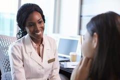 Доктор Wearing Бел Пальто Встреча с женским пациентом Стоковая Фотография