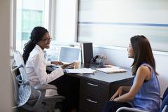 Доктор Wearing Бел Пальто Встреча с женским пациентом Стоковое фото RF