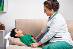 Доктор wonan рассматривает больного школьника ребенка в офисе Стоковые Фото