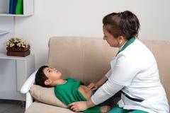 Доктор wonan рассматривает больного школьника ребенка в офисе Стоковые Изображения RF