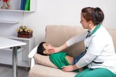 Доктор wonan рассматривает больного школьника ребенка в офисе Стоковое Изображение