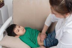 Доктор wonan рассматривает больного школьника ребенка в офисе Стоковые Изображения