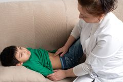Доктор wonan рассматривает больного школьника ребенка в офисе Стоковое Фото