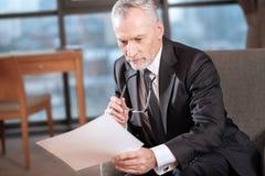 Документы красивого старшего бизнесмена рассматривая Стоковые Фото