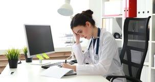 Документы молодого доктора заполняя полагаясь на одной руке сток-видео