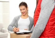 Документы подписания молодой женщины после получать пакет от курьера дома Стоковое Изображение RF
