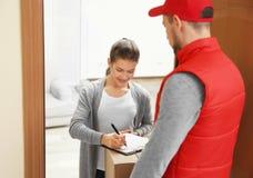 Документы подписания молодой женщины после получать пакет от курьера дома Стоковые Изображения RF