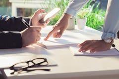Документы подписания бизнесмена и smartphone использования пока коллега указывая на бумаги Стоковые Изображения