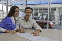 Документы подписания пар для нового автомобиля Стоковое фото RF