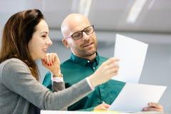 Документы чтения бизнесмена и коммерсантки в офисе Стоковые Изображения