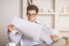 Документ молодого инженера рассматривая Стоковая Фотография RF