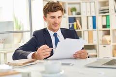 Документ чтения бизнесмена в офисе Стоковые Фотографии RF