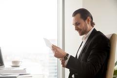 Документ чтения бизнесмена на столе в офисе Стоковое Изображение RF