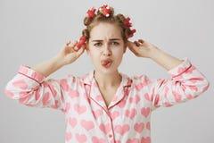 Докучанная и сфокусированная милая кавказская девушка в волос-curlers, нося pyjamas пока в ванной комнате, хмурящся и показывающ  стоковое изображение