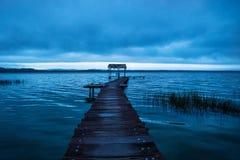 Док пристани водя к хате вдоль берега озера перед заходом солнца, El Remate, Peten, Гватемалой Стоковые Изображения