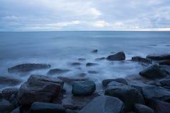 Долгая выдержка воды пляжа на скалистой береговой линии океана стоковое изображение rf