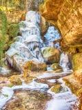 Долгая выдержка замороженного водопада Замороженный поток между мшистыми утесами Стоковое Фото