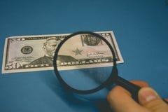 Долларовая банкнота 50 на голубой предпосылке будучи изучанным через лупу стоковое изображение