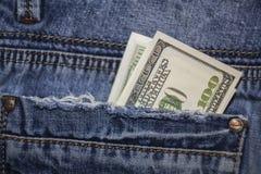 Долларовые банкноты американца 100 в заднем карманн голубых джинсов Стоковое Фото