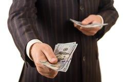 Долларовые банкноты в руках людей, изолированных на белизне Стоковые Изображения