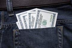 100 долларовых банкнот вставляют из заднего карманн джинсов Стоковые Изображения RF