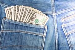 100 долларовых банкнот вставляя в заднем карманн сини джинсовой ткани Стоковое Изображение RF