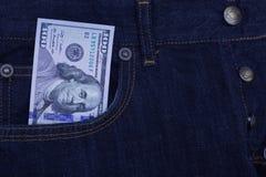 100 долларовых банкнот вставляя из карманн джинсов джинсовой ткани Стоковая Фотография