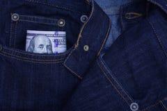 100 долларовых банкнот вставляя из карманн джинсов джинсовой ткани Стоковые Изображения RF