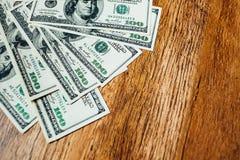 100 долларовых банкнот на деревянной предпосылке Стоковое Изображение