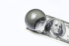 100 долларовых банкнот под шариком лупы проверенное схематическое фото изолированное на белой предпосылке Стоковые Фото