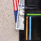 100 долларов банкноты достигают вне из черного старого портмона Стоковые Изображения
