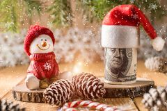 100 долларов банкноты с снеговиком в красной крышке Стоковые Фотографии RF