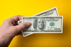 200 долларов в руке на желтой предпосылке, конце-вверх стоковые изображения rf