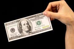 100 долларов в руке на черной предпосылке Стоковое Фото