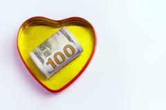 100 долларов в сердце золота сформировали коробку с красным планом против светлой предпосылки Концепция для St Valentin праздника Стоковые Изображения