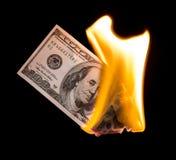 100 долларов горят в огне на черной предпосылке Стоковые Изображения