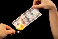 100 долларов горят в руке на черной предпосылке Стоковое Фото