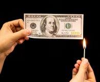 100 долларов горят в руке на черной предпосылке Стоковое Изображение