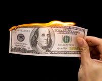 100 долларов горят в руке на черной предпосылке Стоковое Изображение RF
